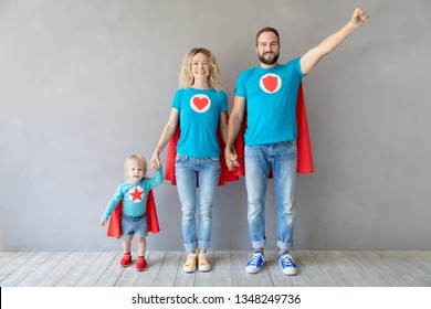 Family of superheroes playing at home. Father, mother and kid having fun together. Parents with child pretend to be a super heroes
