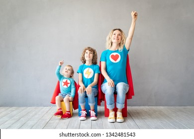 Family of superheroes playing at home. Mother, daughter and son having fun together. Parent with children pretend to be a super heroes. Mother's day concept