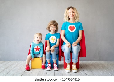 Family of superheroes playing at home. Mother, daughter and son having fun together. Parents with children pretend to be a super heroes