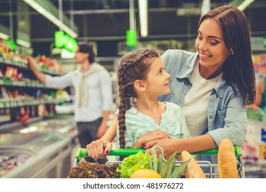 Family in the supermarket. Beautiful young mom and her little daughter are looking at each other and smiling, in the background dad is choosing goods