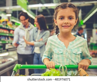 Family in the supermarket. Cute little girl is looking at camera and smiling, in the background her parents are choosing goods
