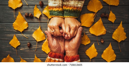 Family support. Autumn couple embrace hands top view,fall ash  leaf,Autumnal mood,  relationship   concept