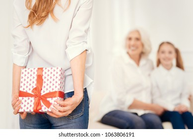 Family surprise. Selective focus on a turned back adult woman in casual looking at her smiling mother and daughter while holding a present behind her back and congratulating them.