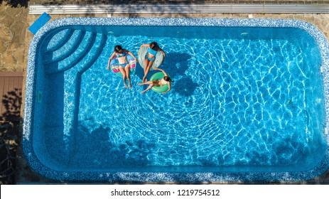 Familia en la piscina vista aérea de drones desde arriba, madre feliz y niños nadan en inflables donuts de anillo y se divierten en el agua en vacaciones familiares, vacaciones tropicales en el resort
