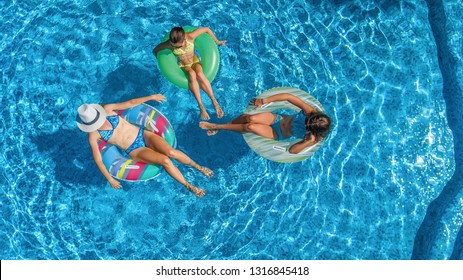 Family in swimming pool aerial drone view from above, happy mother and kids swim on inflatable ring donuts and have fun in water on family vacation, tropical holidays on resort