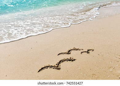Family symbol - three seagulls drawing on the sand on the golden sunny sandy beach in the resort on summer vacation rest. Background with soft waves. Symbol of freedom, ease, rest.