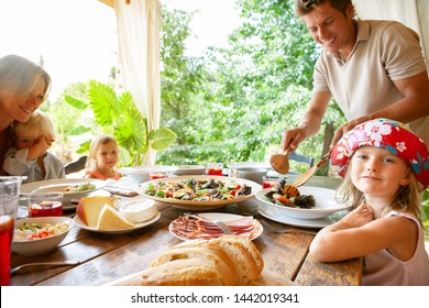 Family at table eating healthy mediterranean fresh food together, in holiday villa garden, tropical outdoors. Parents and children having lunch, eating on exotic vacation smiling, leisure lifestyle.