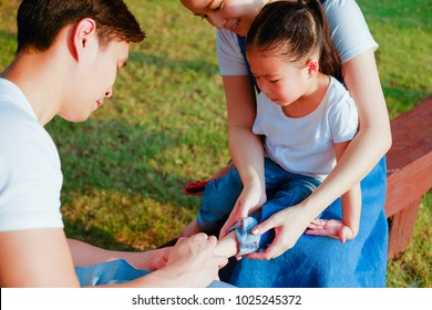 Family take care small child girl naughty in playground until her have lesion on the feet