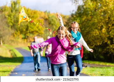 Family take walk in autumn forest flying kite