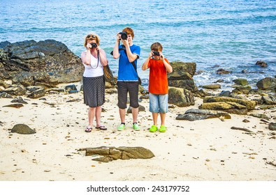 family takes a photo at the rocky beach with ocean in background
