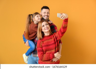 Family taking selfie on color background