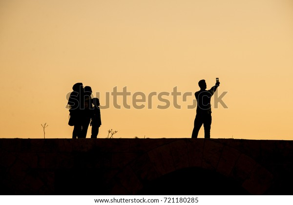 A family taking selfie on top of Kizkalesi castle while sunset