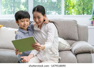 Family taking a selfie photo while sitting on sofa at home. mother and sons take a selfie with smartphone happy sitting on couch.