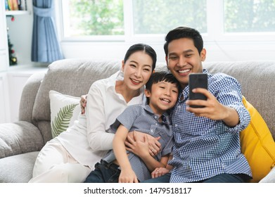 Family taking a selfie photo while sitting on sofa at home. Father, mother and sons take a selfie with smartphone happy sitting on couch.