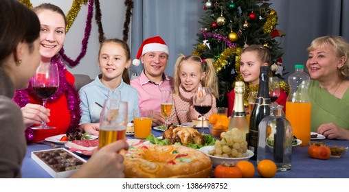 Family is talking toasts and drinking in time celebration New Year at home.