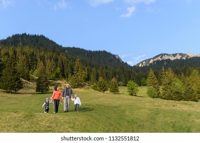 family talking and walking on meadow at forest