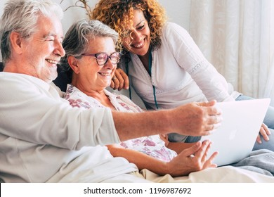 family team at work at home sit down on the sofa. smile and have fun working on a laptop together. mother father and daughter aged senior use technology and internet at home. cheerful caucasian people