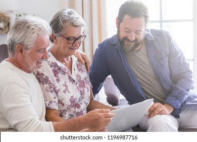 family team at work at home sit down on the sofa. smile and have fun working on a laptop together. mother father and son aged senior use technology and internet home. cheerful caucasian people modern