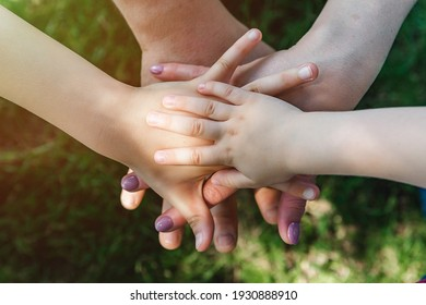 family teamwork, hands on top of each other top view, summer sports mood. Close up