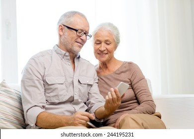 family, technology, age and people concept - happy senior couple with smartphone at home