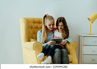 Family. Technology. Education. Mom and daughter are using a digital tablet and smiling while sitting in an armchair at home