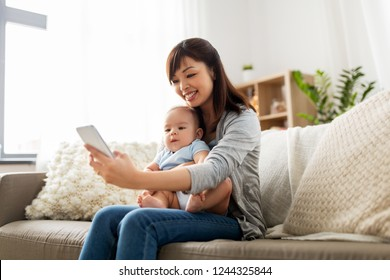 family, technology and motherhood concept - happy young asian mother with little baby son taking selfie by smartphone at home
