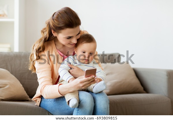 family, technology and motherhood concept - happy smiling young mother with little baby and smartphone at home