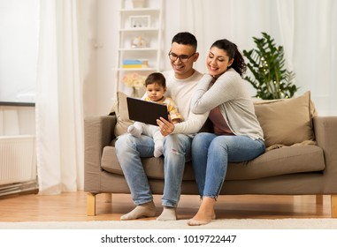 family, technology, parenthood and people concept - happy mother and father showing tablet pc computer to baby daughter at home