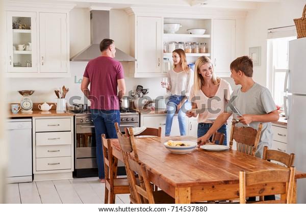 Familie mit Kindern im Teenageralter, die einen Tisch für Mahlzeiten in der Küche reservieren