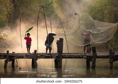 The family of Thai people in the northeast has a simple life. Helping to catch fish in the river on a wooden bridge with mother, father and daughter.