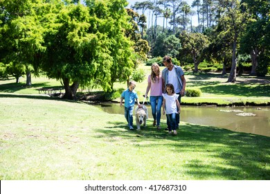 Family with their dog walking in the park near a pond