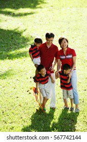 Family with three boys, standing on field, looking at camera