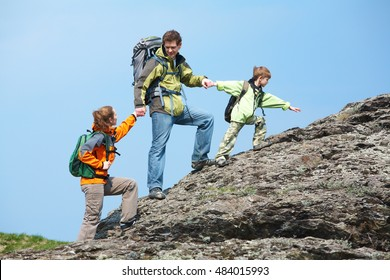 A family of three climbing up the top of a mountain holding hands