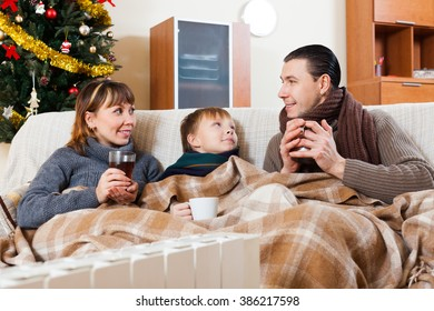 family of three with cups of tea warming near warm radiator in Christmas time