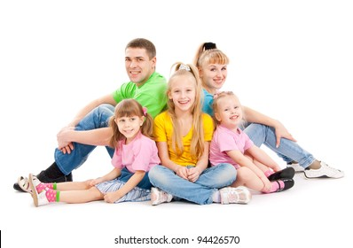Family with three daughters sit on a floor, a white background