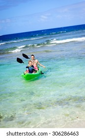 A family of three: father and his son and daughter having fun kayaking in the ocean