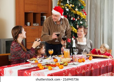 family of three generations  celebrating Christmas  over holiday table at home
