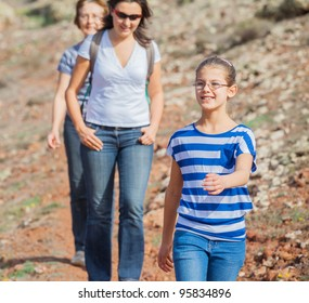 Family of three - girl, mother and grandmother hiking in the cross-country