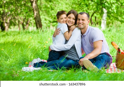 Family of three has picnic in park. Concept of happy family relations and carefree leisure time