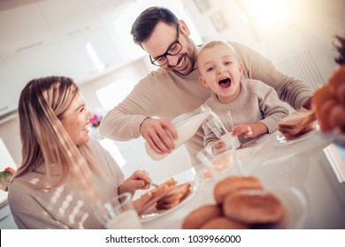 Family of three having breakfast in the morning together in their home.