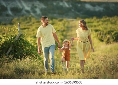 Family of three mom dad and daughter walking in a grape field.
