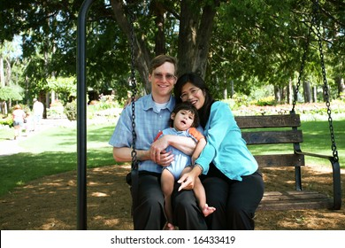 Family of three on swing