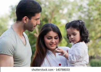 family of three in outdoor, young couple with daughter in the outdoors.