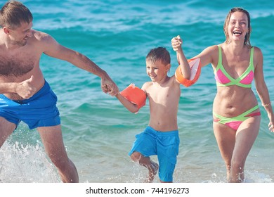 Family of three people getting out from the sea water. Front view.