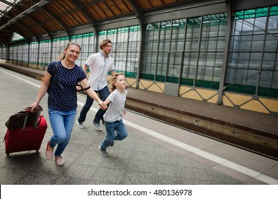 Family of three people hotfoot on platform of railway train station. They are late for a train. Mum holds the son by the hand. Adults roll greater suitcases.