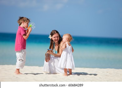 Family of three playing on tropical beach and making soap bubbles