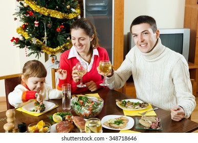 Family of three posing for  Christmas portrait around festive table at home