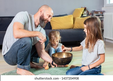 Family of three Practice Tibetan bowls sound therapy. The healing sound vibration.Father and two daughters plays with Tibetan singing bowl and other musical instruments