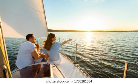 Family Of Three Sailing On Yacht Sitting On Sailboat Deck Looking At Sunset At Seaside. Dream Vacation Concept. Free Space
