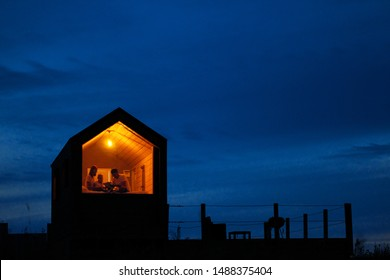 A family of three is sitting on a bed by the window, reading a book and talking. View of the outside of the house. Night blue sky. Orange warm light from an incandescent lamp. The concept of home
